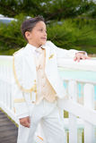 Young First Communion boy leaning on a white wooden fence Royalty Free Stock Photo