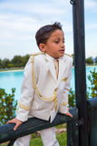 Young First Communion boy leaning on a wooden fence Royalty Free Stock Image