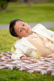 Young First Communion boy lying on a blanket outdoors Stock Photo