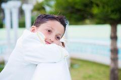 Young First Communion boy smiling and leaning on a white wooden Stock Photography