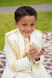 Young First Communion boy smiling with prayer book and rosary. Young boy with white sailor suit in his First Communion smiling with a prayer book and rosary in Stock Photos