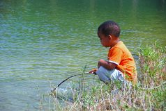 Young Fisher. A toddler african american boy sits by the lake with a small stick used to fish Stock Photos