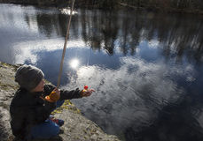 Young fisher checking bait Royalty Free Stock Photo