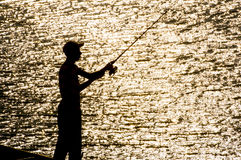 Young fisher silhouette. In the lake Stock Photography
