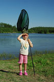 A young fisherman. A young girl standing by the lake with landing nets Stock Photography