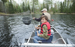 A young fisherman in a canoe smiles seeing walleye Stock Image