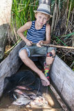 Young fisherman with a catch. Young fisherman sits in a wooden boat with a catch holding a fishing rod Stock Images