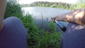 A fisherman catches fish on a river bank with a fishing rod in summer. A young fisherman catches fish on a river bank with a fishing rod in summer. He keeps a stock footage