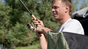 Fisherman catching fish and spinning fishing reel during biting. Young fisherman catching fish and spinning fishing reel during biting on summer background. Man stock video