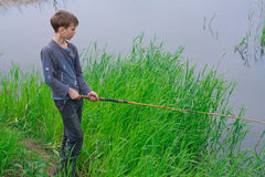 Young fisherman with a fishing rod royalty free stock photo