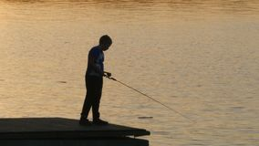 Young fisherman with a fishing rod silhouette. Against the background of the evening river stock footage
