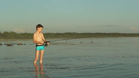 Young fisherman on the lake fishing. stock footage