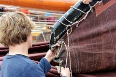Young fisherman makes his ship ready to sail, Volendam,Holland Stock Image
