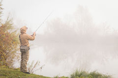 Young fisherman. On the river bank. Fisherman caught a zander and holds it in his hands Royalty Free Stock Photo