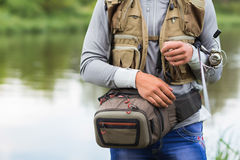 Young fisherman. On the river bank. Fisherman caught a zander and holds it in his hands Royalty Free Stock Image