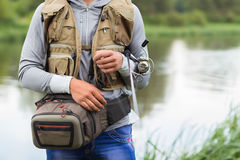 Young fisherman. On the river bank. Fisherman caught a zander and holds it in his hands Royalty Free Stock Images