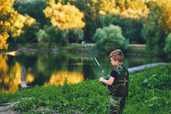 Young fisherman on the river with a fishing rod Royalty Free Stock Images