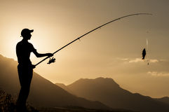 Young fisherman silhouette. Fisherman.Sunset.Sun.Mountains.Landscape.Younger fisher.Sugla Leke fish activities.Fishing activities.Relaxing and active sport royalty free stock image