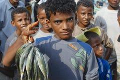 Young fishermen demonstrate catch of the day, Al Hudaydah, Yemen. Stock Photo