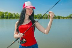 Young fisherwoman preparing for fishing. Girl with fishing rod. Looks at lure royalty free stock photography