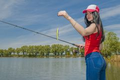 Young fisherwoman preparing for fishing. Girl with fishing rod looks at lure.  royalty free stock image