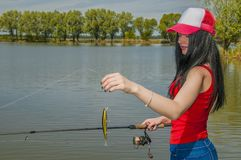Young fisherwoman preparing for fishing. Girl with fishing rod looks at lure.  royalty free stock images