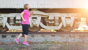 Young Fit Adult Woman Jogging Outdoors Listening To Music Royalty Free Stock Photos