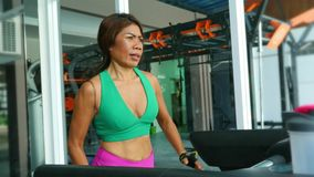 Young fit and athletic Asian Thai woman with fit body running on gym treadmill sweating training hard jogging workout stock footage