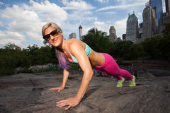 Young  fit Athletic woman exercising in Central Park Stock Photo