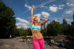 Young fit Athletic woman exercising in Central Park. Young Blonde fit Athletic woman exercising in Central Park Royalty Free Stock Photo