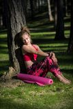 Young fit athletic woman in a forest wearing smart watch sitting on the ground next to yoga mat. Mind and body concept. Stock Photos