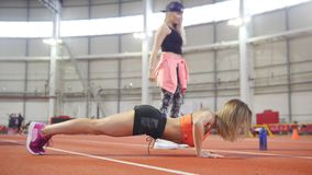 Young fit athletic woman in sports clothes doing push ups. Another woman doing squats stock video