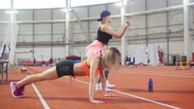 Young fit athletic woman in sports clothes doing push ups. Another woman in leggins doing squats stock footage