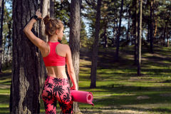 Young fit athletic woman wearing smart watch and holding yoga mat, ready for her workout in a forest. Mind and body happiness. Concept stock photos