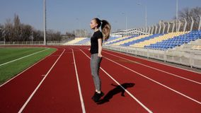 Young fit attractive active woman jumping with skipping rope working out warming up at big stadium on sunny spring day stock footage