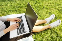 College student girl sitting on the green lawn doing homework on her laptop computer. Young woman sitting at the park blogging, wr. Young fit attractive hipster Royalty Free Stock Photos