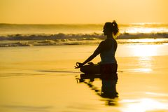 Young fit and attractive sport woman in beach sunset yoga practice workout sitting on wet sun in front of the sea in meditation an. D relaxation exercise in mind royalty free stock photo