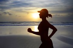 Young fit and attractive woman in American cap training on sunset beach doing running fitness workout under a beautiful sky in stock image