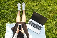College student girl sitting on the green lawn doing homework on her laptop computer. Young woman sitting at the park blogging, wr. Young fit attractive woman Stock Photography
