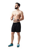 Young fit bearded athlete holding water container looking up. Full body length portrait isolated over white studio background Royalty Free Stock Photo