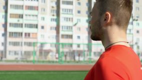 Fit bearded man walks on stadium lawn stock video footage