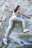 Young fit beautiful girl climbing outdoor on a artificial rock royalty free stock image