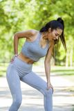 Young fit beautiful girl got back injury during outdoor exercise royalty free stock image
