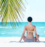 Young, fit and beautiful girl meditating on a summer beach Royalty Free Stock Image