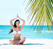 Young, fit and beautiful girl meditating on a summer beach Royalty Free Stock Photo