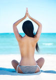 Young, fit and beautiful girl meditating on a summer beach Stock Image