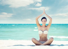Young, fit and beautiful girl meditating on a summer beach Royalty Free Stock Images