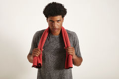 Young fit black athlete grabbing red towel on his neck stock photography