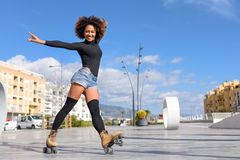 Black woman on roller skates riding outdoors on urban street. Young fit black woman on roller skates riding outdoors on urban street with open arms. Smiling girl Royalty Free Stock Image