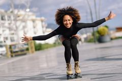 Black woman on roller skates riding outdoors on urban street. Young fit black woman on roller skates riding outdoors on urban street with open arms. Smiling girl Royalty Free Stock Photos